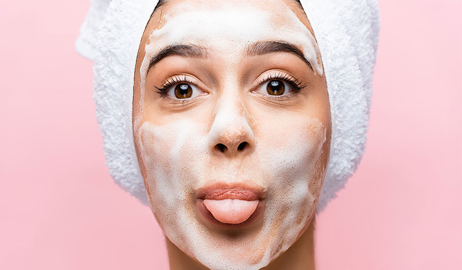 woman with hair in a towel choosing the cleanser she should use
