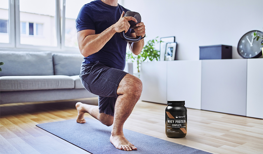 Male working out at home doing lunges with kettlebell