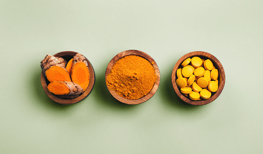 Turmeric in wooden bowls, fresh turmeric root, powdered, pills on green background