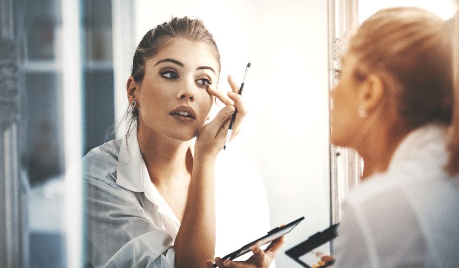woman applying eyeshadow in mirror using eyeshadow palette dupe