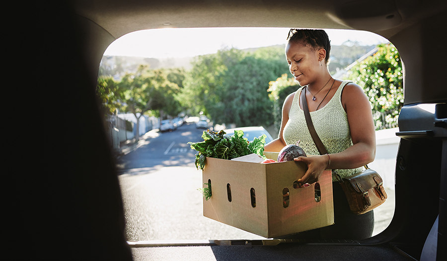 Woman putting healthy groceries in her car