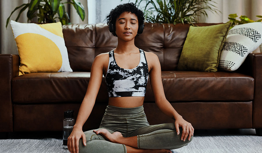 woman sitting on living room floor meditating