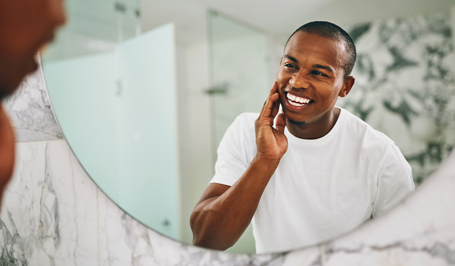 man looking in mirror and smiling after skincare routine