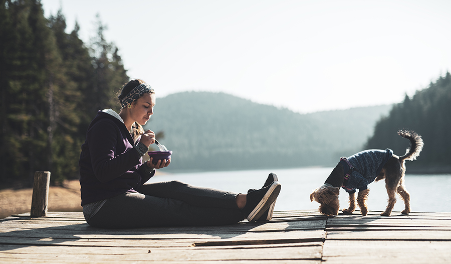 Woman eating healthy food on wooden pier around mountain lake with her dog.