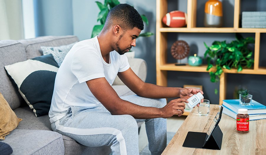 Male looking up supplement ingredients in living room with multivitamin on table