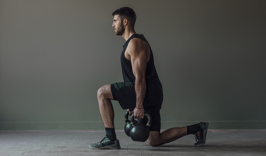Muscular athlete doing lunges with kettlebell weights, strength training