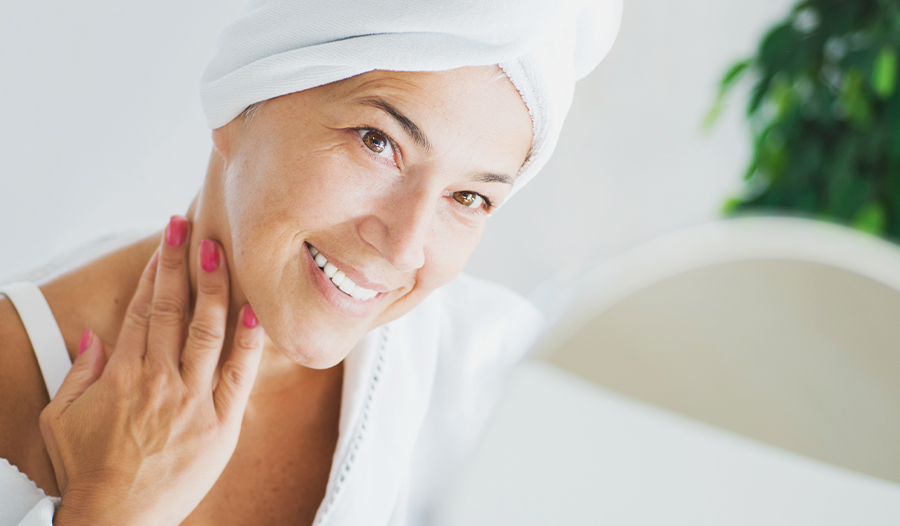 mature woman in bathrobe and hair in a towel looking at skin in the mirror