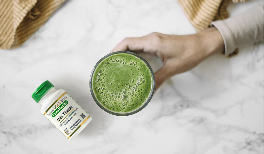 Cup of green juice in hand over marble table with milk thistle supplement bottle