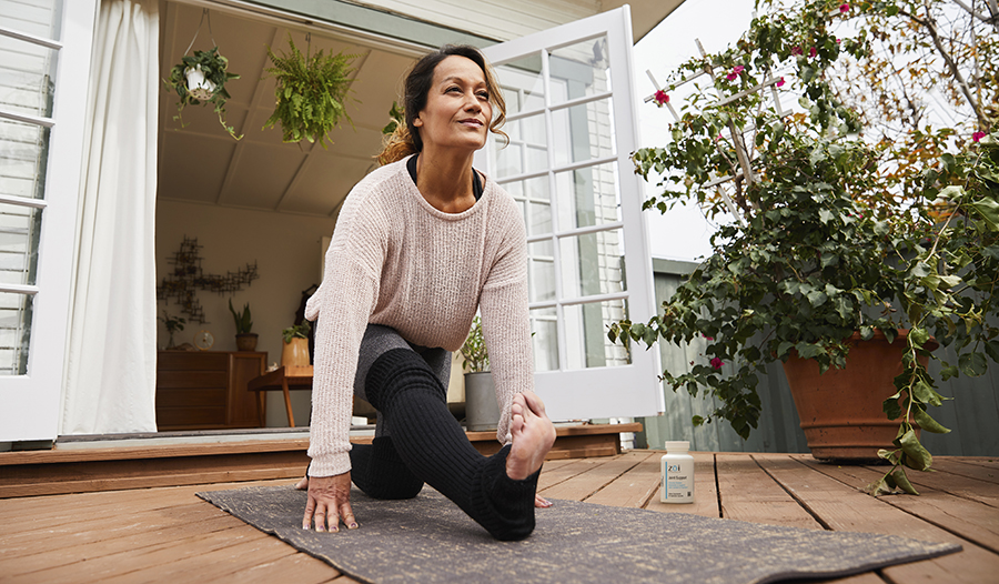 Woman stretching doing yoga on wooden deck in backyard surrounded by green plants
