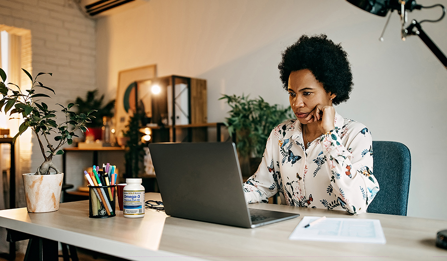 Woman working from home on a laptop while sitting at a desk