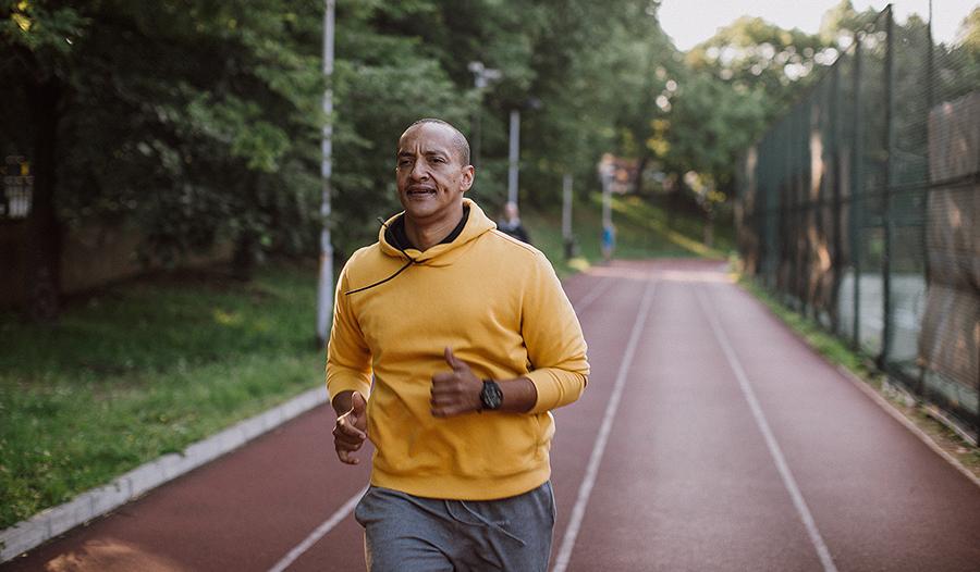 Man in yellow sweatshirt jogging outside on a track