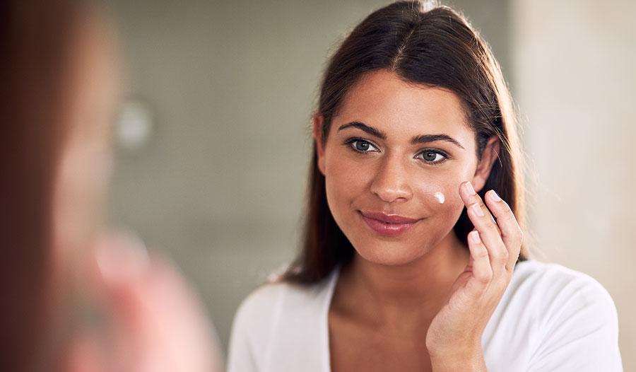 woman applying moisturizer with probiotics to her skin