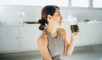 Fit Asian woman resting and having green smoothie after exercising at home
