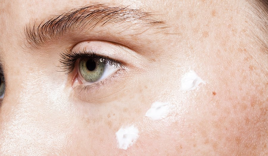 Close up of moisturizing lotion on young woman's face