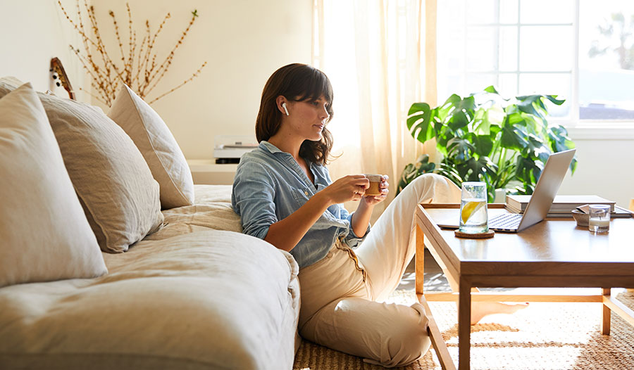 woman sitting on the floor in her living room relaxing and practicing self-care