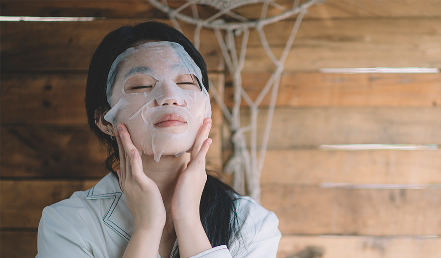 woman putting on sheet mask as part of her self care