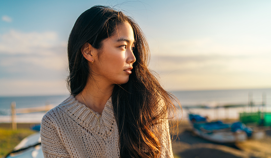 asian woman looking into the distance thinking about self-care