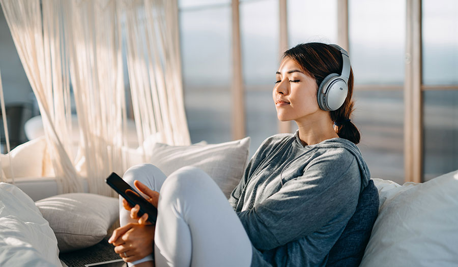 woman listening to music on her headphones while on her balcony