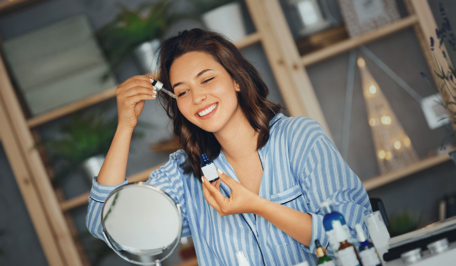 woman applying skincare serum to her face with a dropper