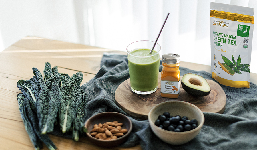 Superfoods on a table like kale, blueberries, turmeric, and green tea