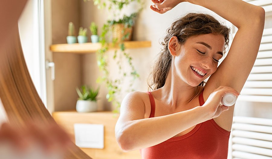 woman applying natural deodorant to her underarms