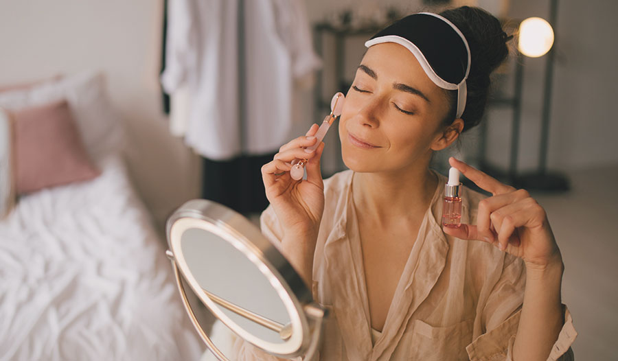 woman using a jade roller to roll some facial serum on her face