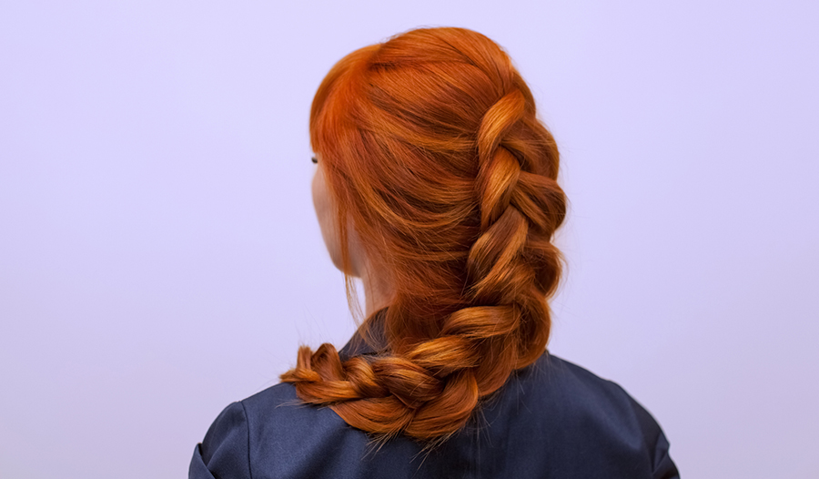 woman with red hair in a braid showing off thick and full hair