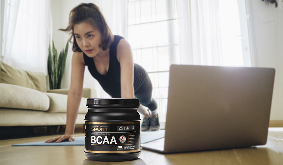Woman working out at home with laptop in living room; BCAAs supplement in foreground