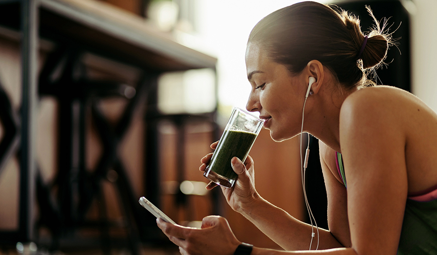 Woman drinking green juice with chlorophyll while looking at her phone