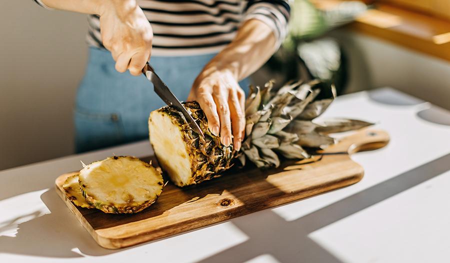 Woman in apron cutting pineapple