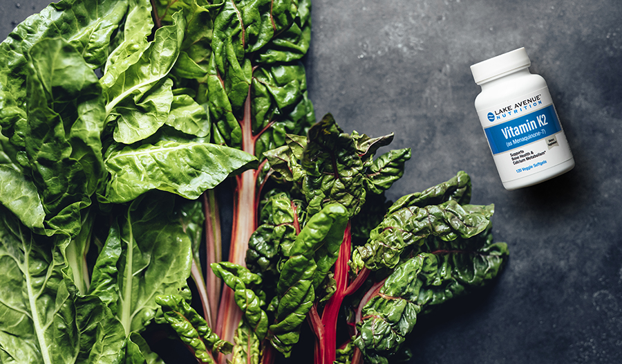 Vitamin K supplement bottle and leafy greens on concrete table