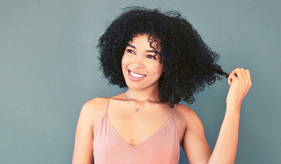 woman with curly hair wonders if she should use shampoos with sulfates