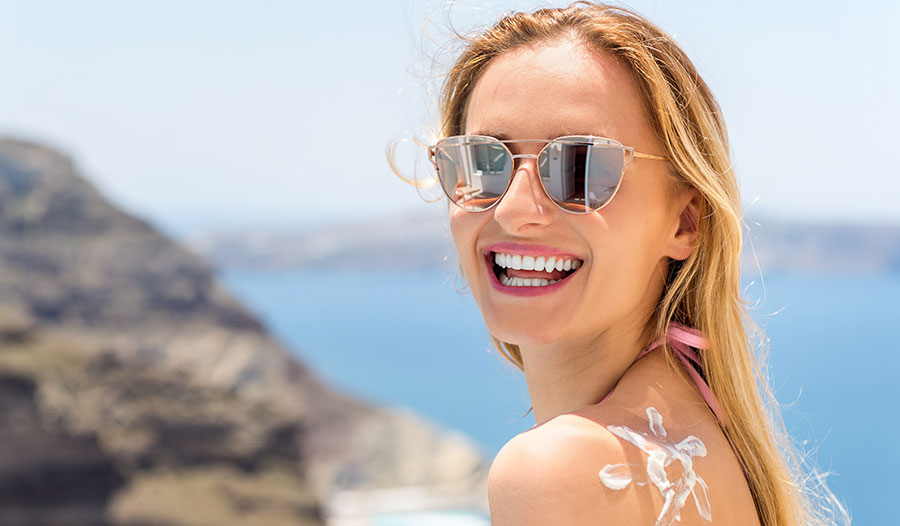 woman wearing sunglasses outdoors with sunscreen on her shoulder