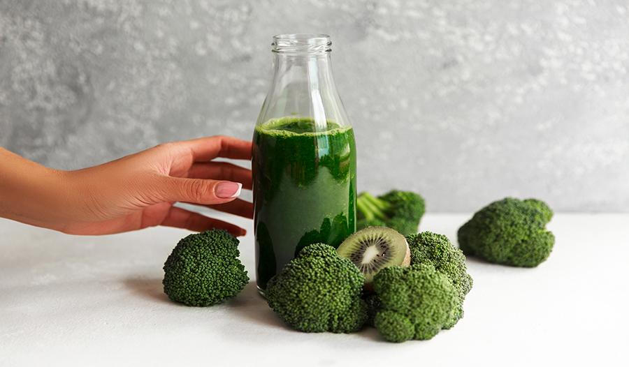 Рука тянется к зеленому соку из брокколи и киви